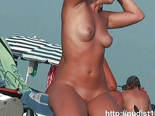 Nude beach voyeur spies on a perky breasted nudist